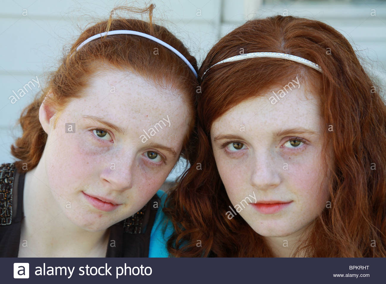 A close up of 14 year old identical twin sisters with red hair. - Stock Image