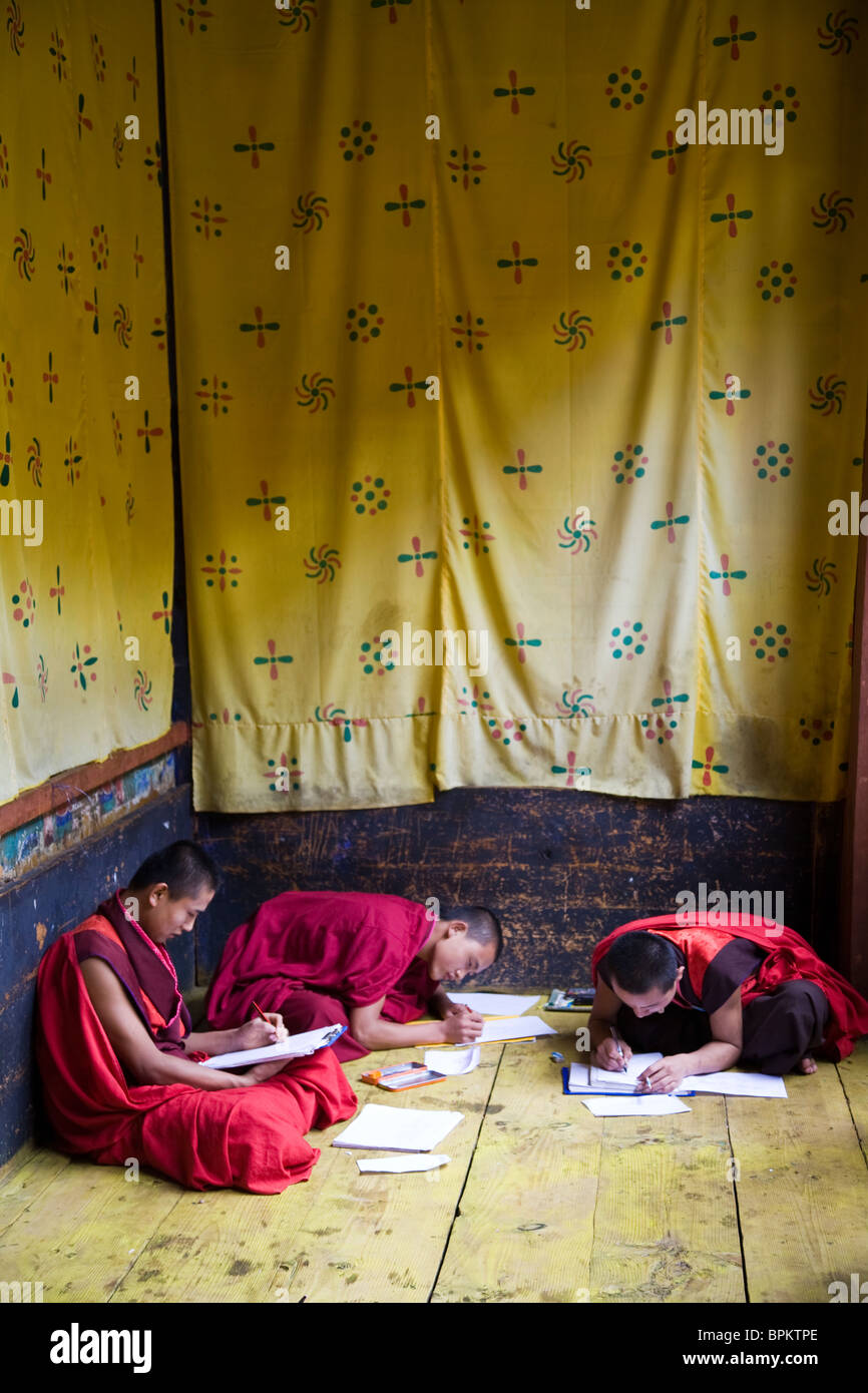 Three Buddhist monks study and write in a room draped with yellow fabric Bhutan Asia - Stock Image