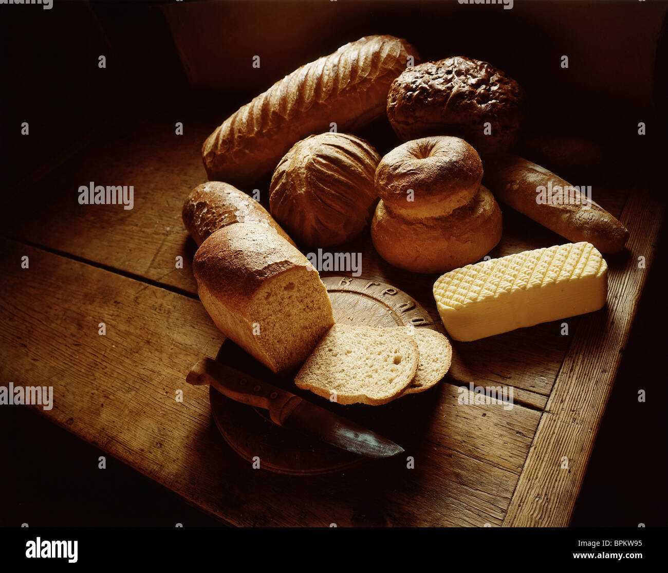 Loaves of bread on table with butter - Stock Image