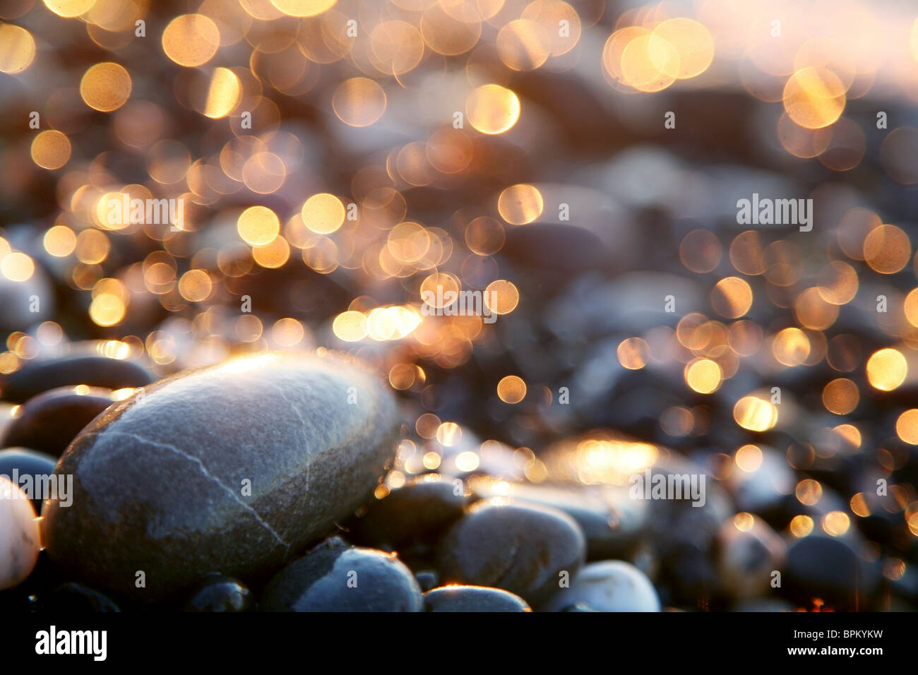 Background with sea stones and orange blurred circles. - Stock Image