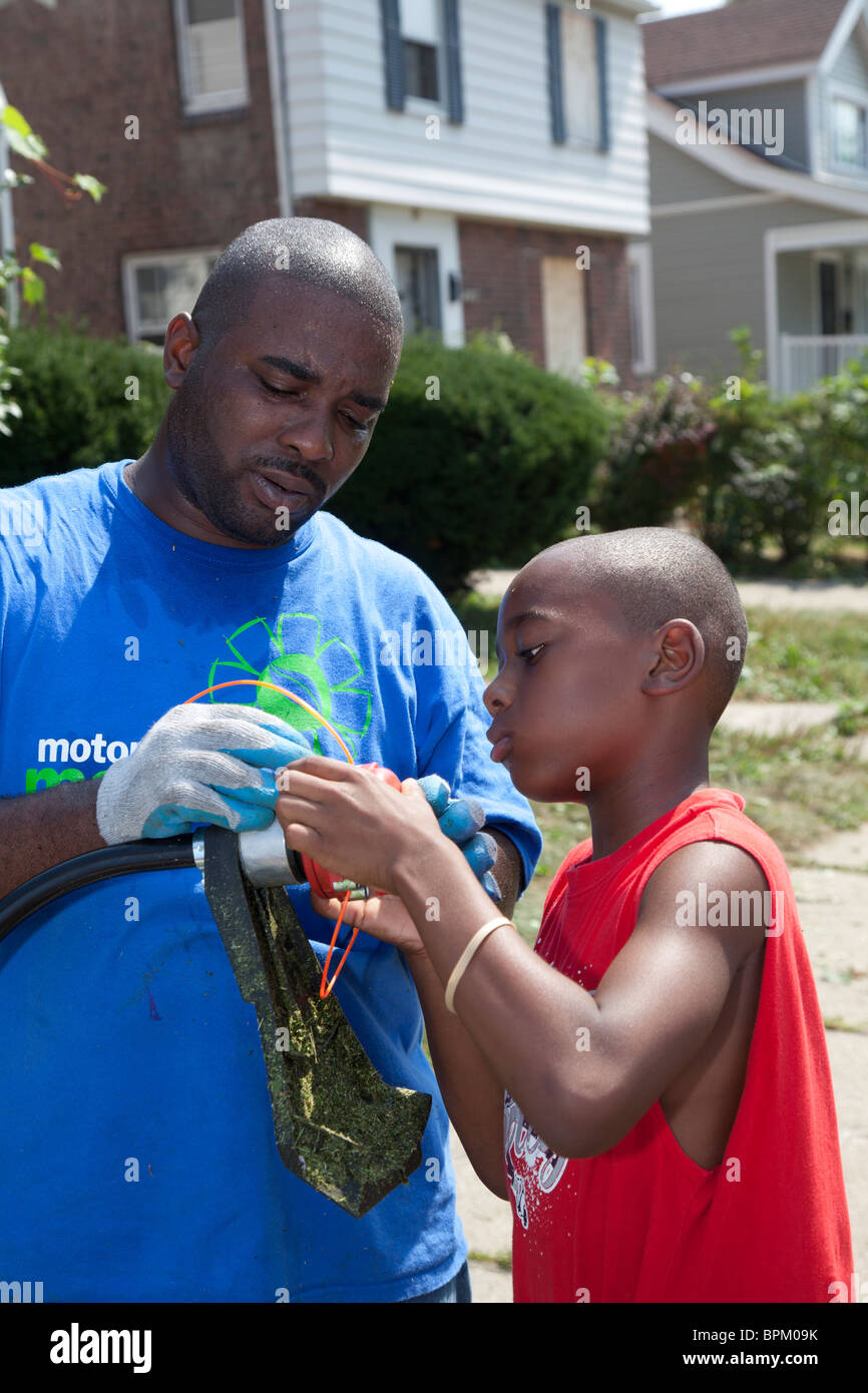 Man and Boy Thread a Line on a String Trimmer - Stock Image