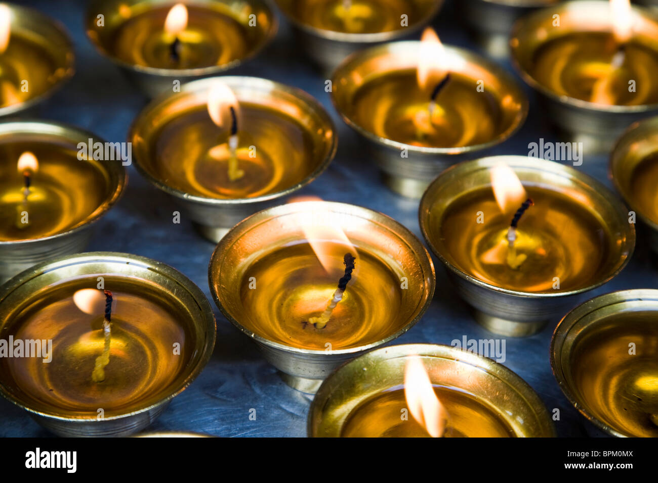 Candles burn in golden colored candle holders Bhutan Asia - Stock Image