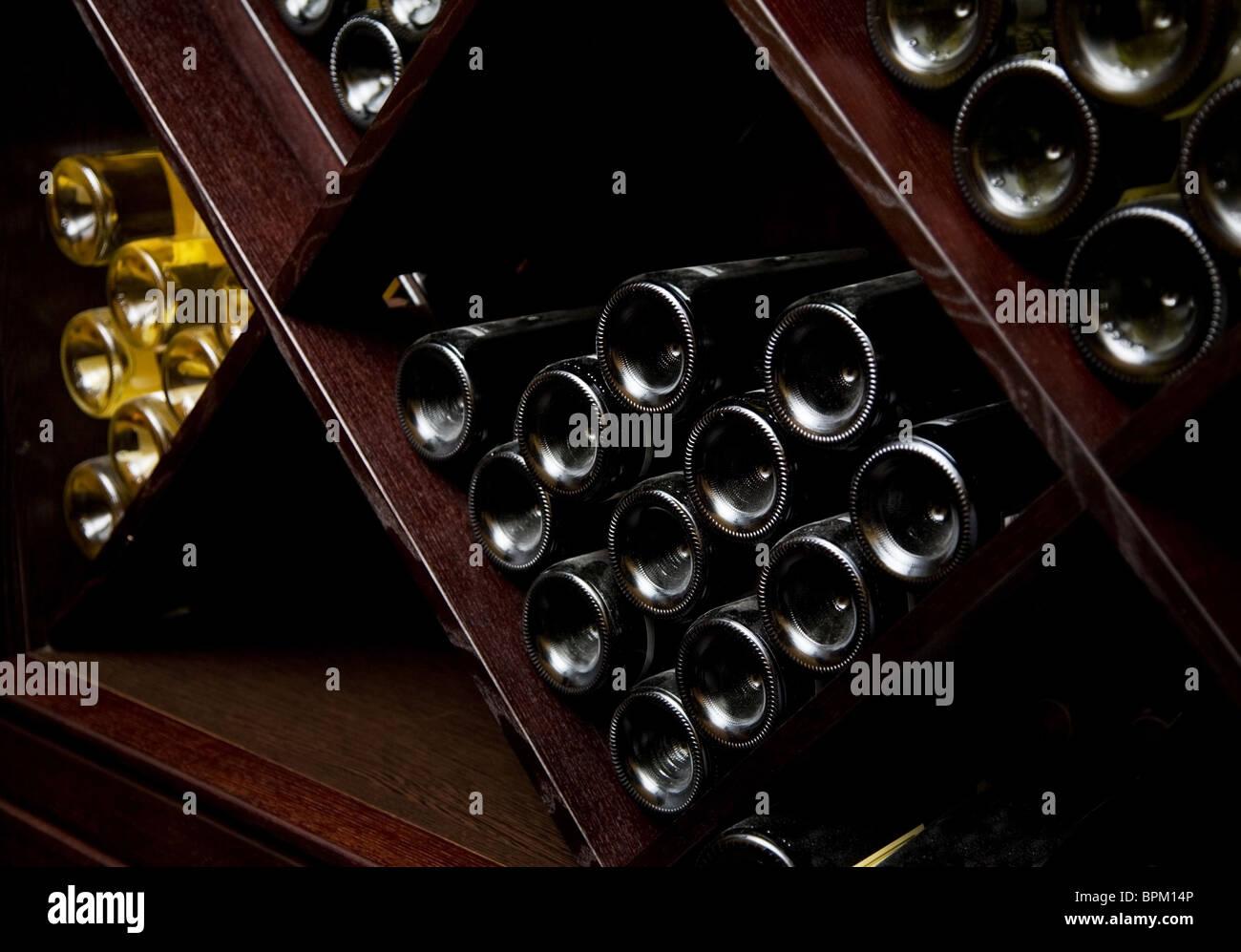 Snapshot of the wine cellar. The bottles on wooden shelves. - Stock Image