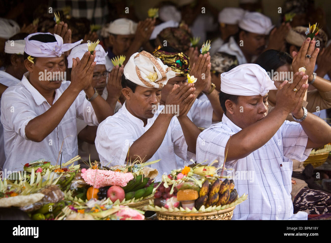 Religious practitioners pray during a ceremony in Bali Indonesia - Stock Image