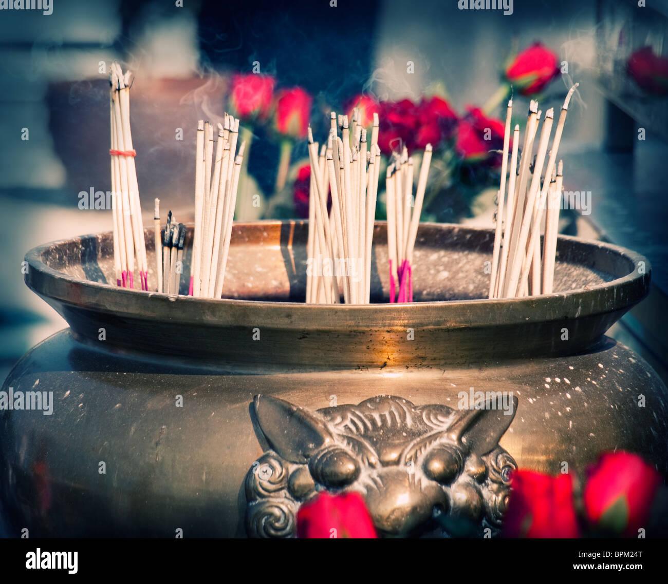 Buddhist shrine with smoking incense sticks and roses, cross-processed image , closeup Stock Photo
