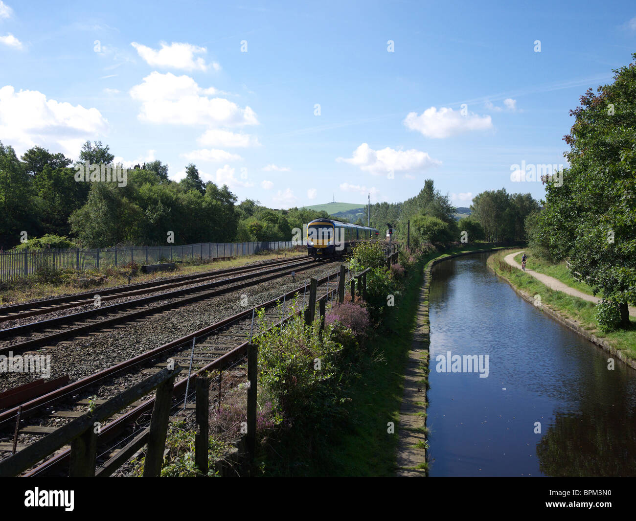 Train and the Huddersfield canal at Diggle, Oldham, England, UK. - Stock Image