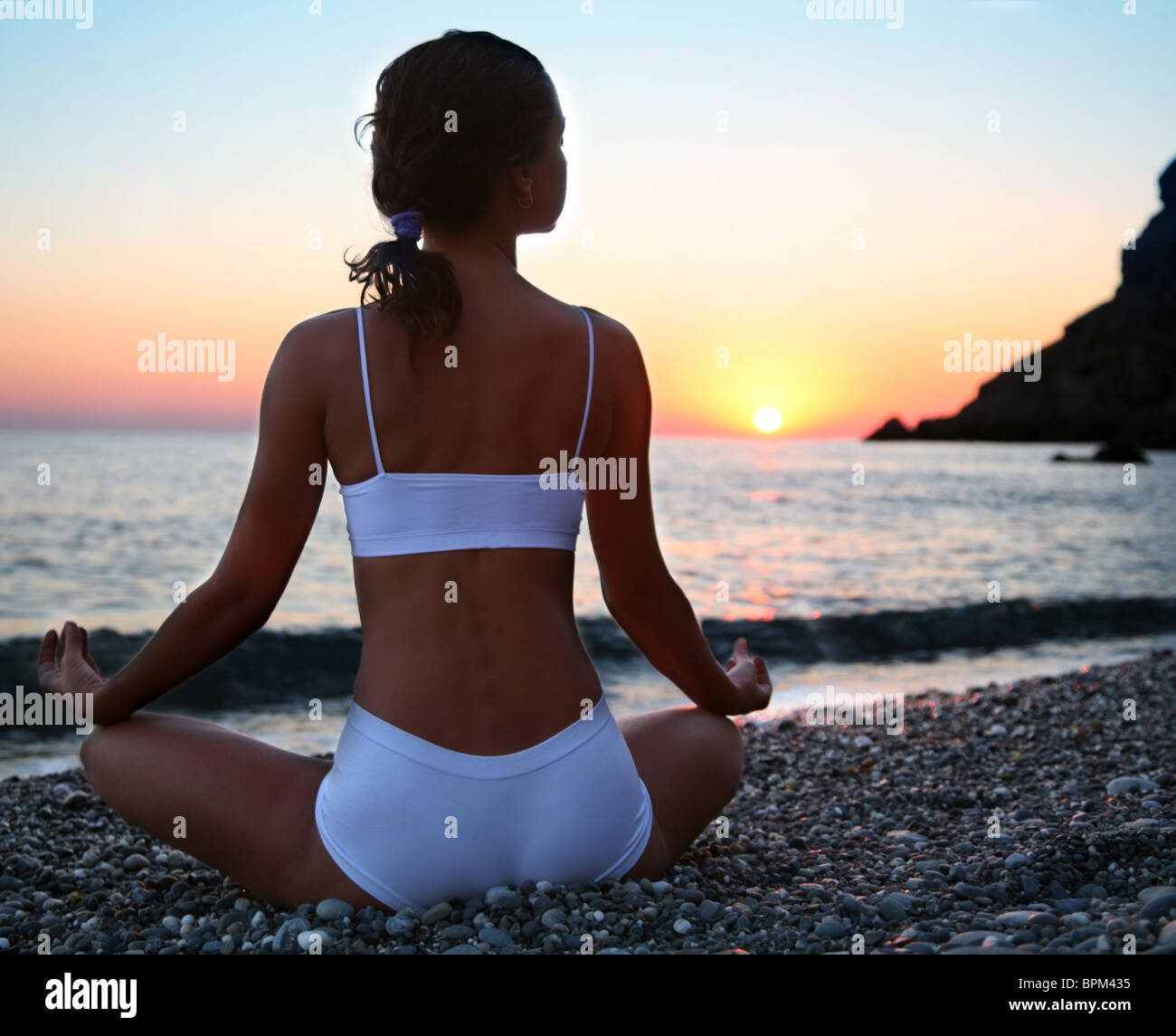 Woman meditating on the beach at sunset. - Stock Image
