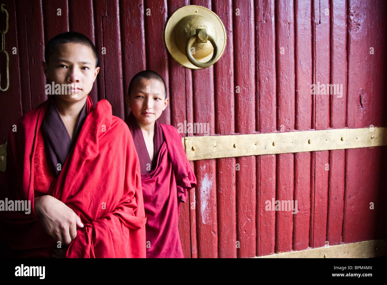 Two young Buddhist monks stand before an ancient monastery door Bhutan Asia - Stock Image