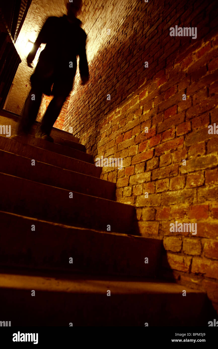Silhouetted man walking down stairs Stock Photo