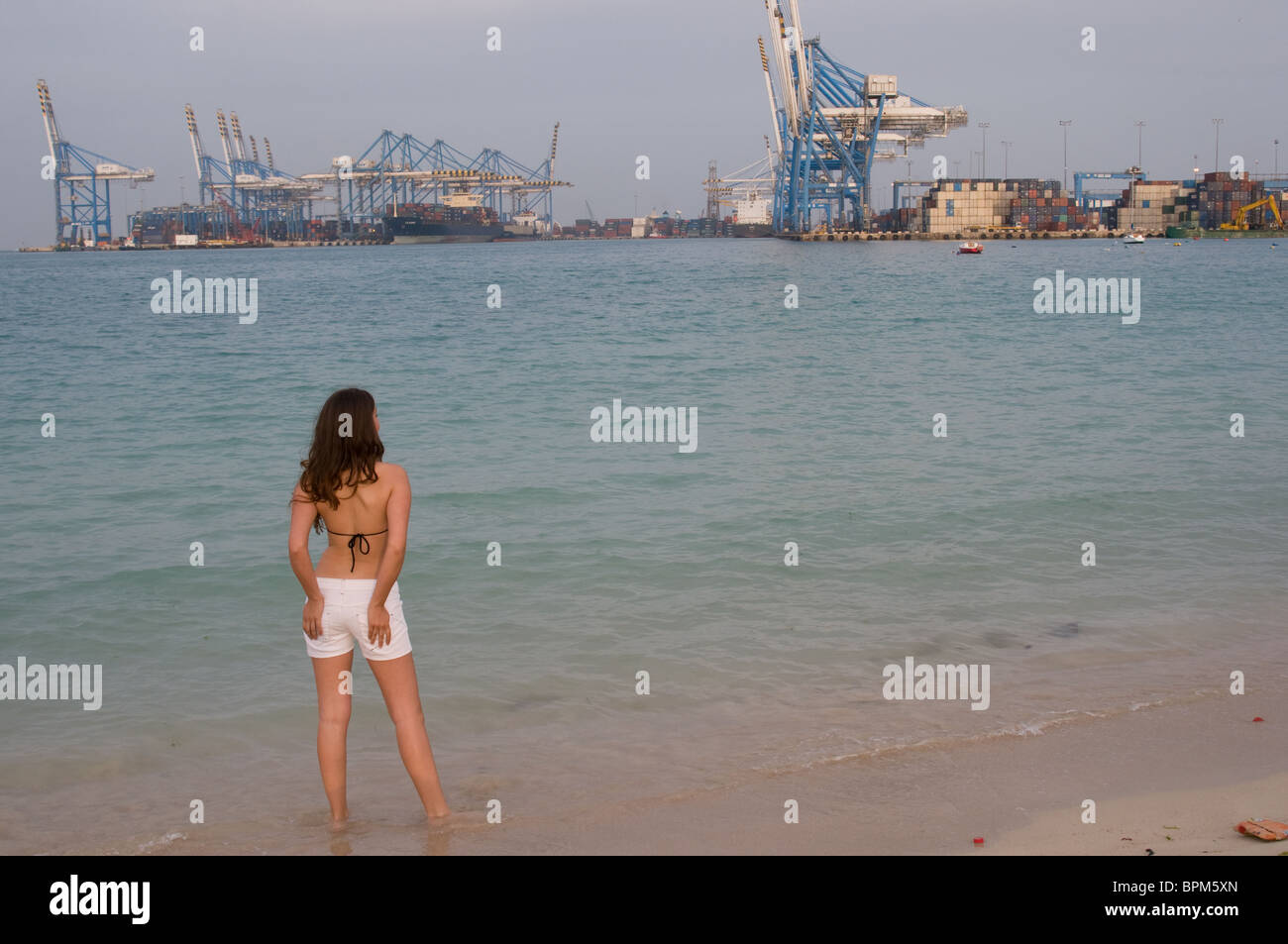 A girl stands on the beach at Pretty Bay, Birzabbugia, Malta looking across to the ships in Freeport docks - Stock Image