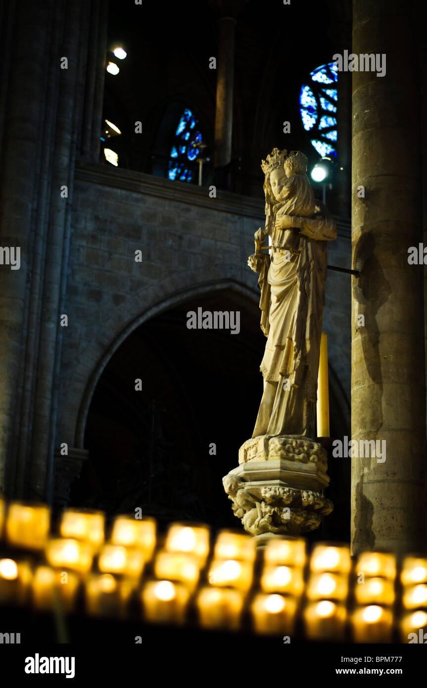 PARIS, France - Candles and statue of Saint Mary inside Notre Dame de Paris - Stock Image