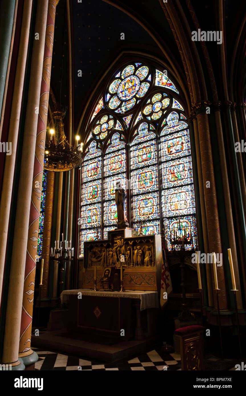 PARIS, France - A chapel inside Notre Dame de Paris, with an altar backed by a stained glass window - Stock Image