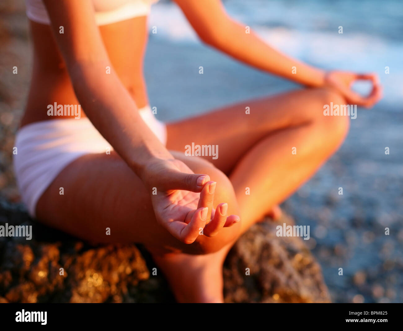 body of a beautiful girl in a meditation on the beach - Stock Image
