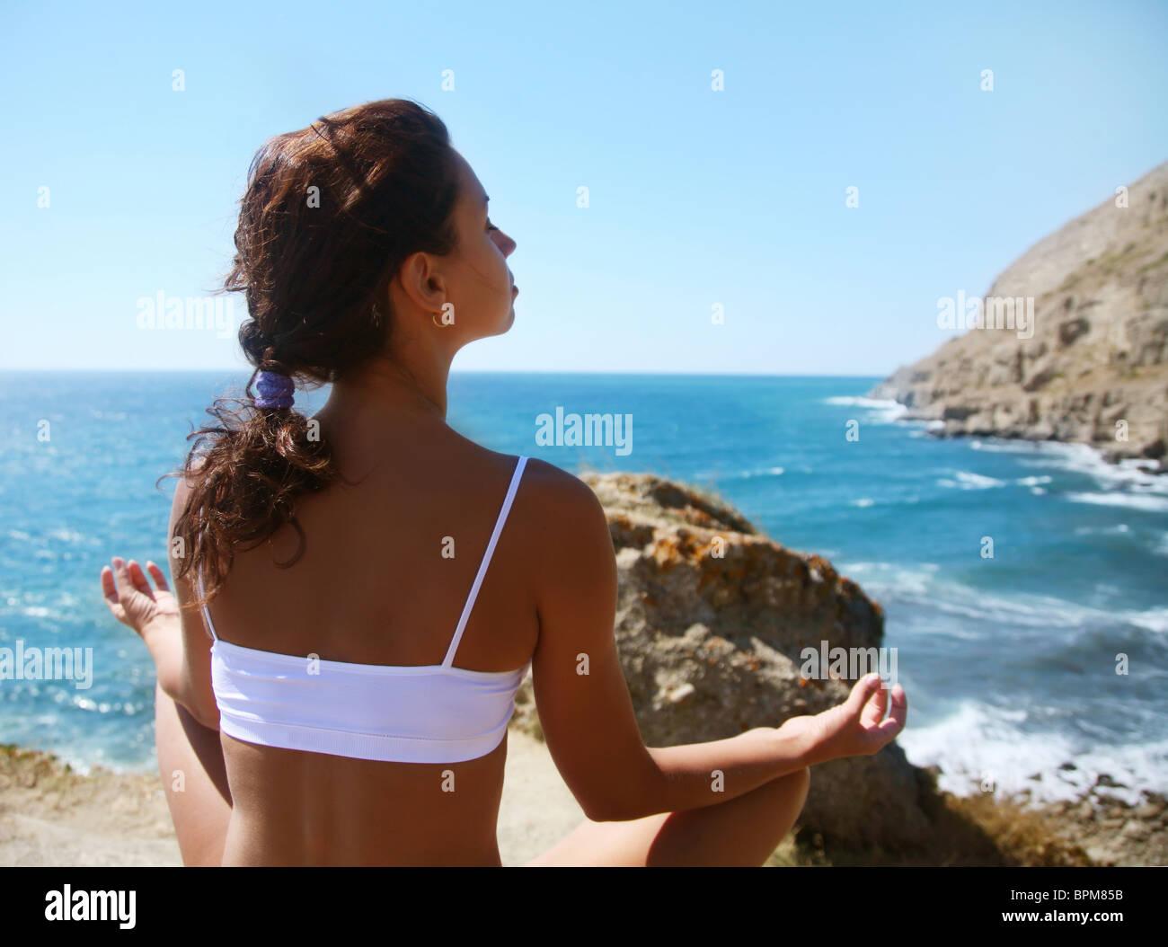Woman meditating on a rocky seashore - Stock Image