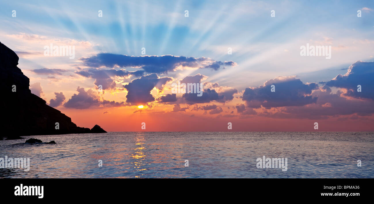 Beautiful landscape from the rising sun and mountains. Rays penetrate the clouds. - Stock Image