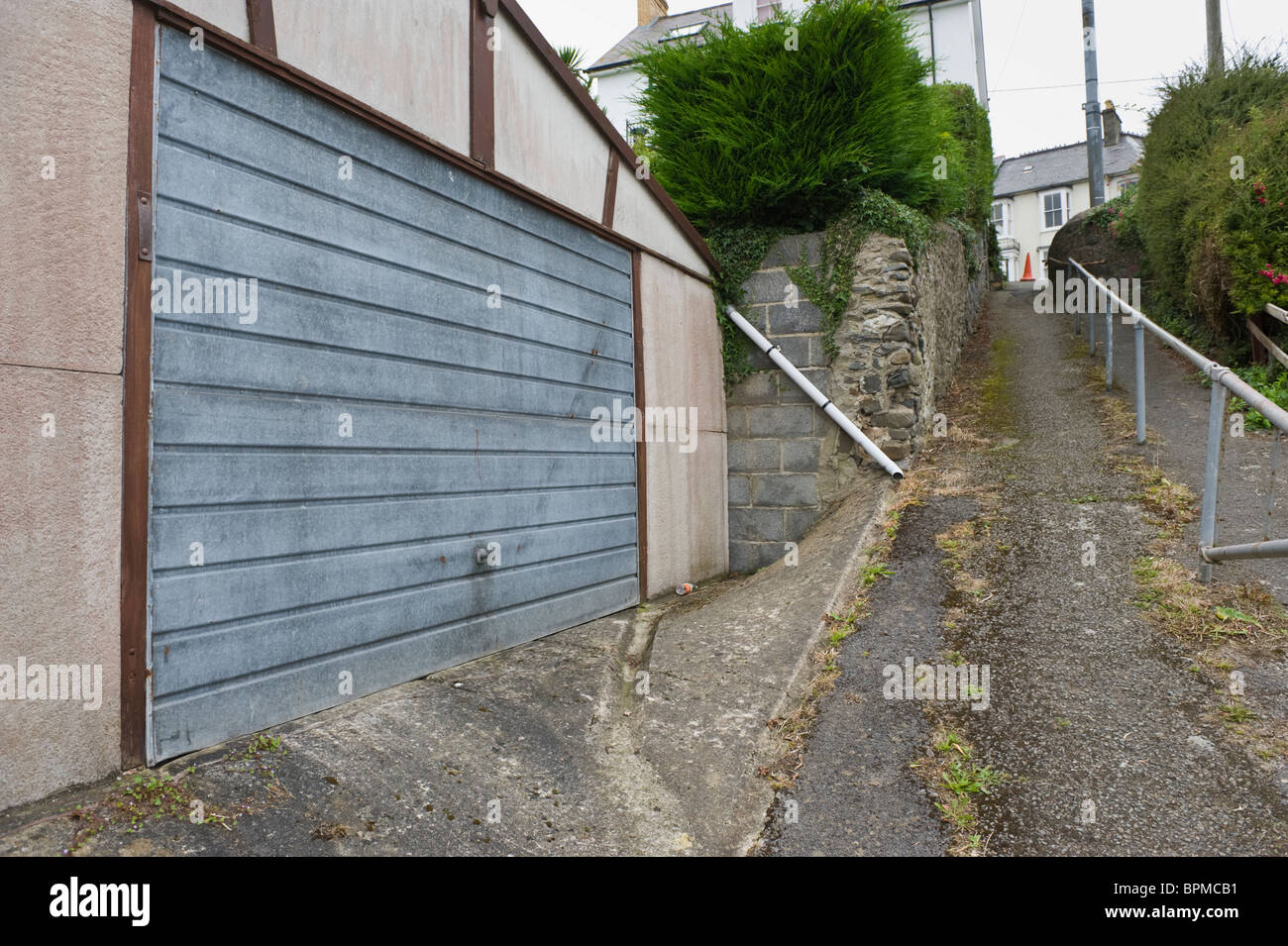 Garage and footpath wth handrail on backstreet in coastal town of New Quay Ceredigion West Wales UK - Stock Image