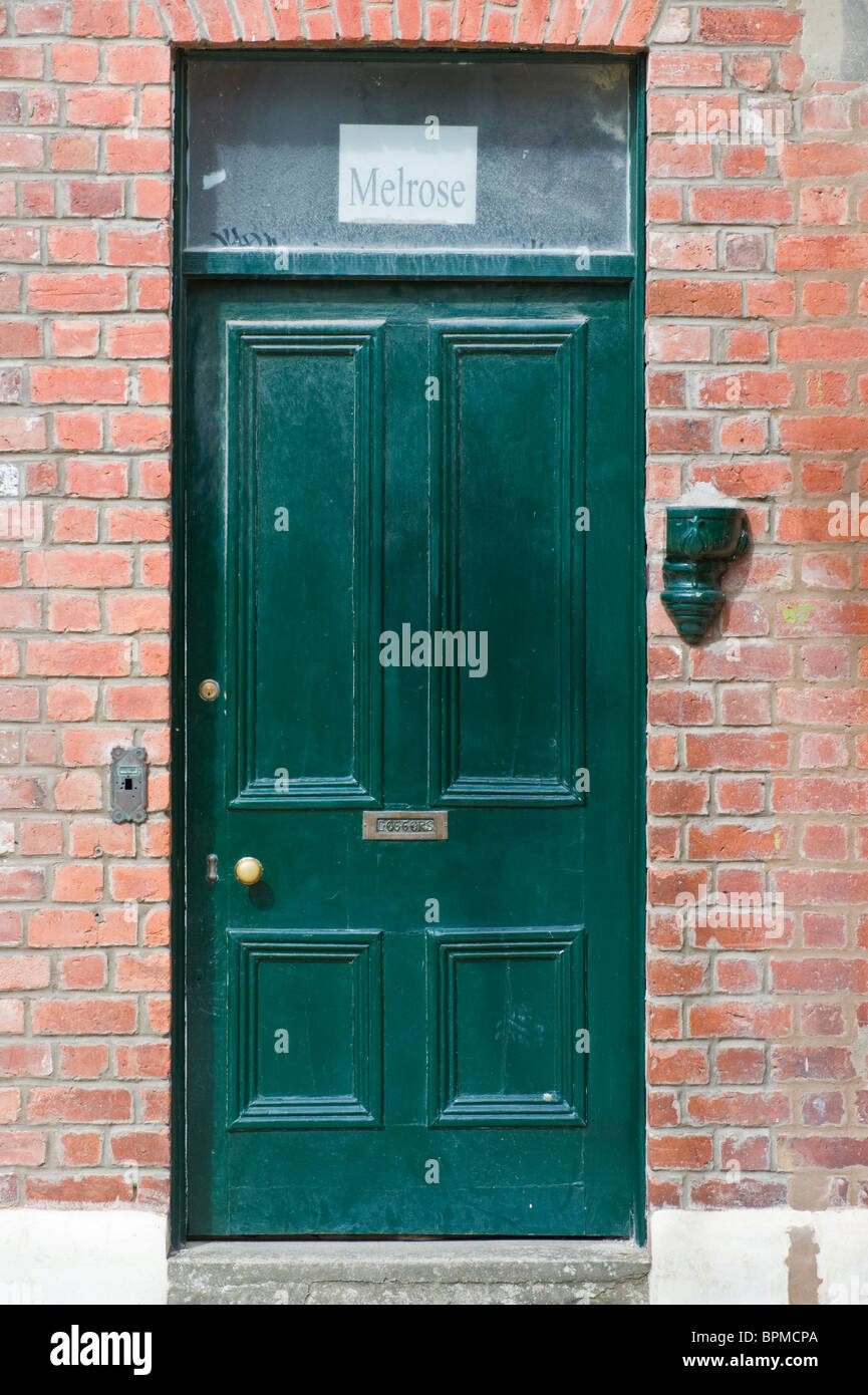 Victorian paneled green front door of brick built terraced house in Llandrindod Wells Powys Mid Wales UK Stock Photo