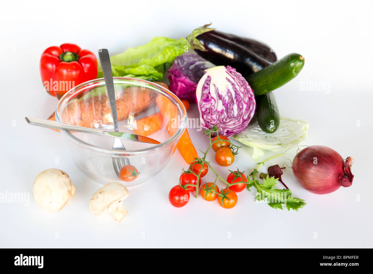 Fresh vegetables and an empty salad bowl. Whole uncut salad ingredients on white background - Stock Image