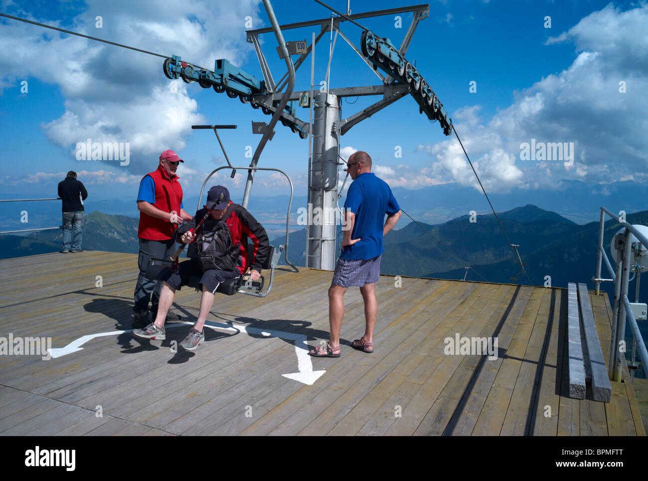 A man gets off a two seat ski lift near the summit of Chopok Mountain Low Tatras Slovakia - Stock Image