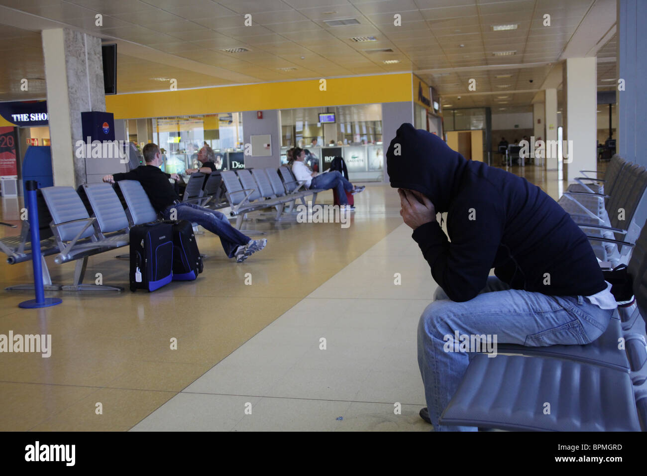 A man head-in-hands on some seats in Girona airport in Spain waiting for a delayed flight - Stock Image