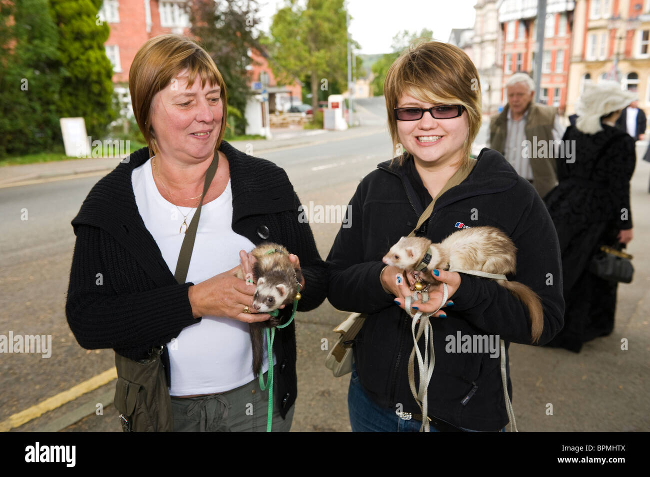 Two women holding tame pet ferrets walking through Llandrindod Wells Powys Mid Wales UK - Stock Image