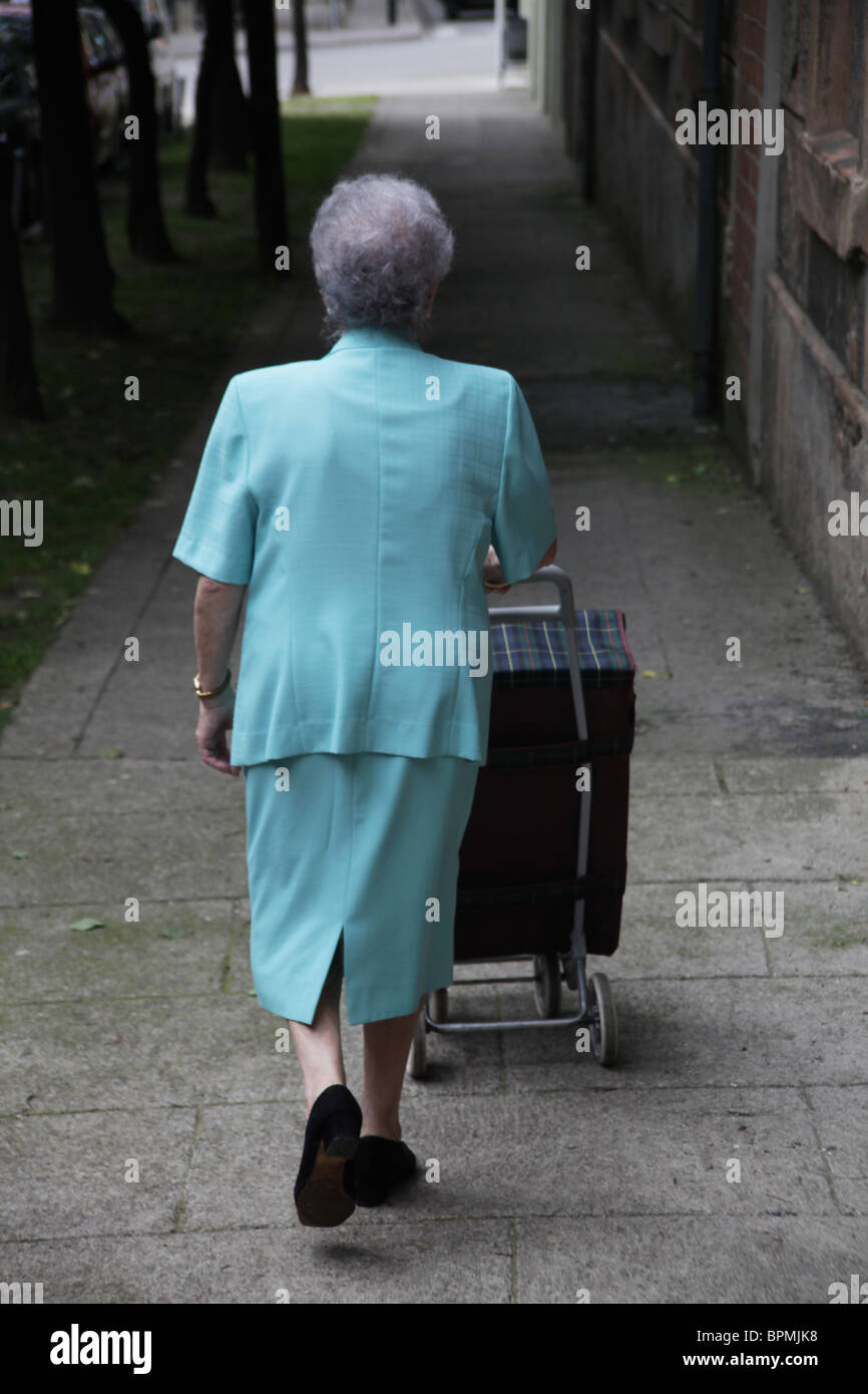 Old lady with a shopping trolley goes shopping in Spain - Stock Image