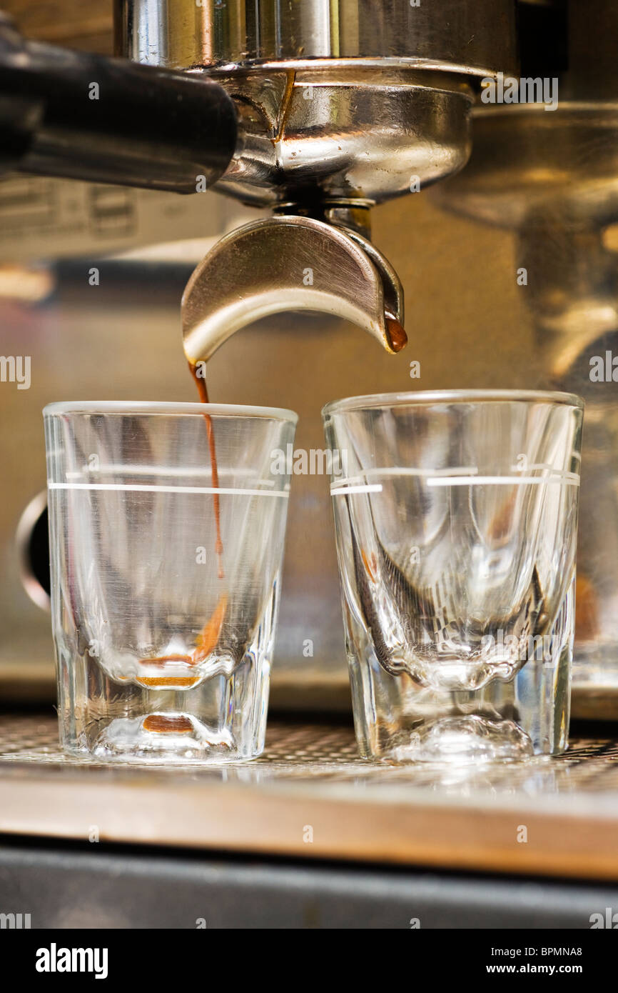 Close-up of espresso machine and shot glasses during a pour. - Stock Image