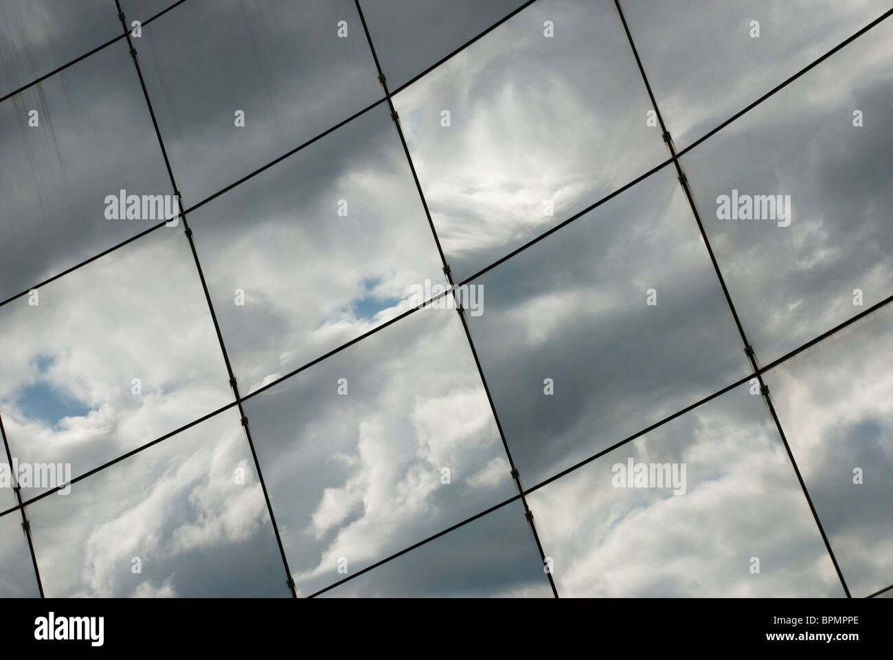 Clouds reflected on the glass wall 2 - Stock Image