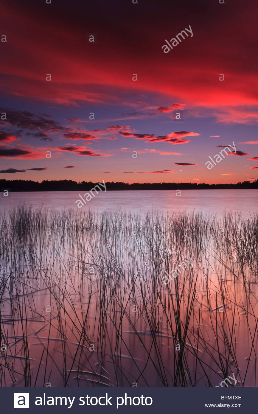 Colorful skies at sunset, at Huggenes in the lake Vansjø, Rygge kommune, Østfold fylke, Norway. - Stock Image