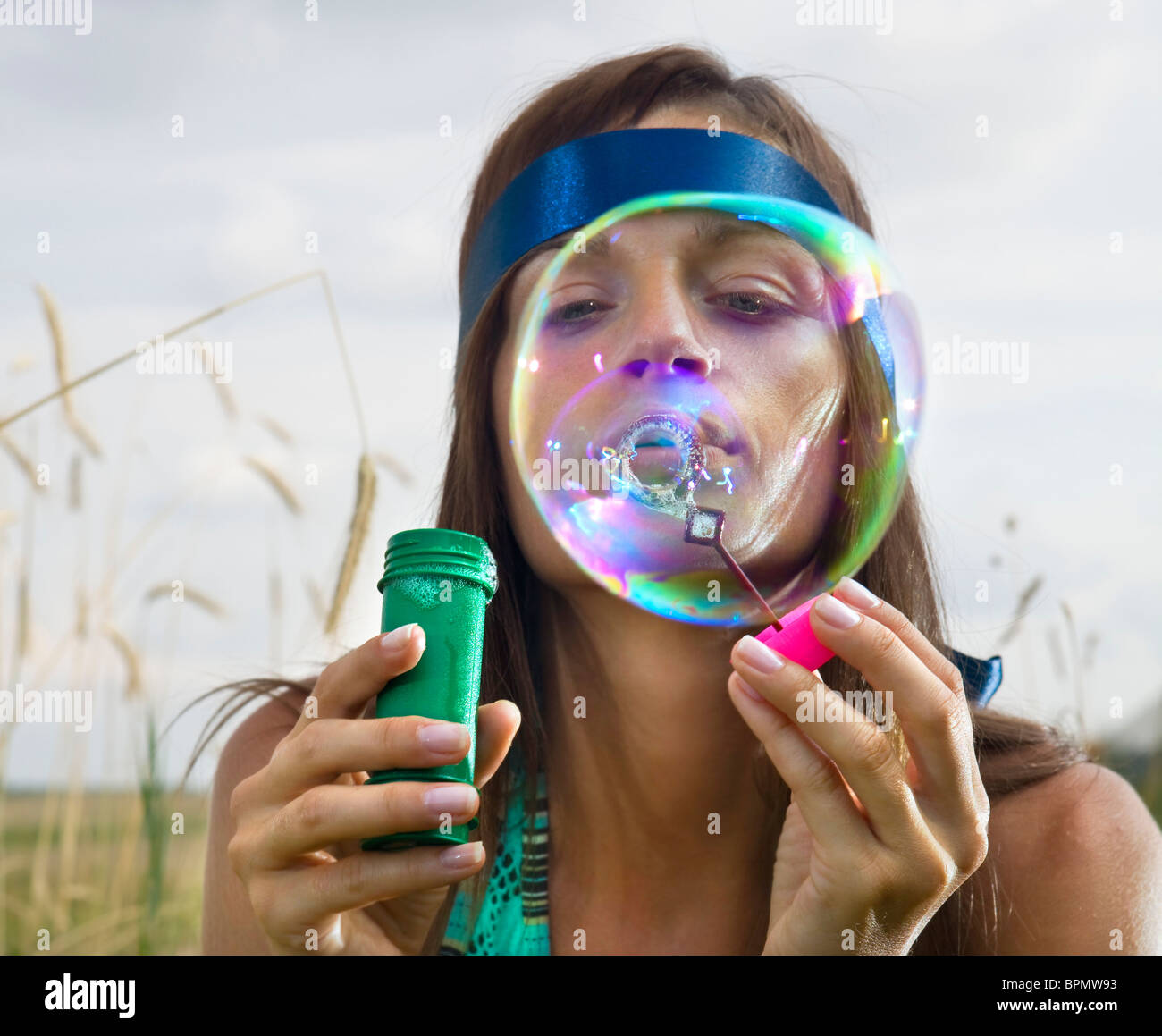 beauty young woman blowing soap bubbles in summer day - Stock Image
