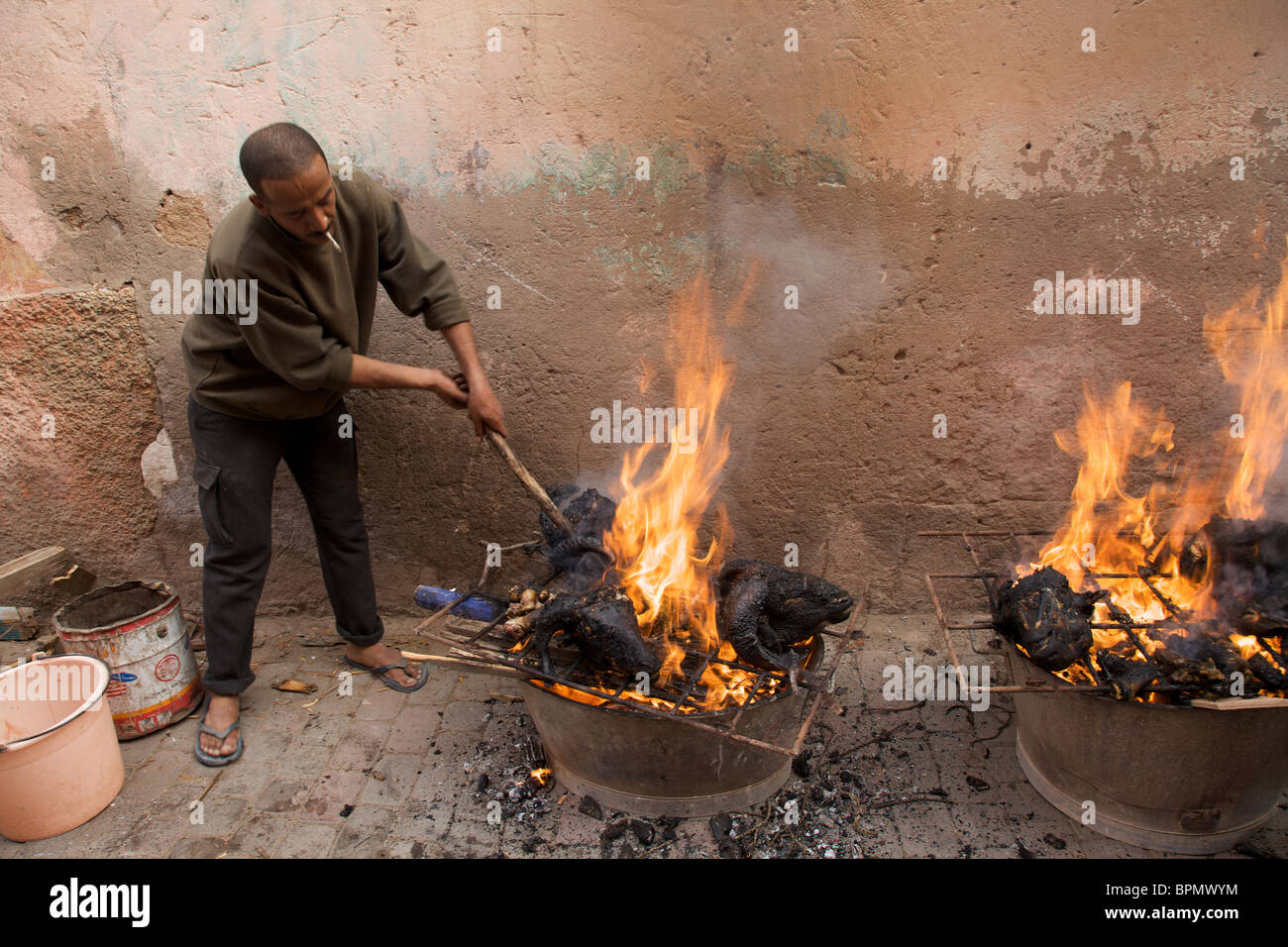 A man stoking the bbq's on the day of Eid al-Adha, Marrakech, Morocco  North Africa - Stock Image
