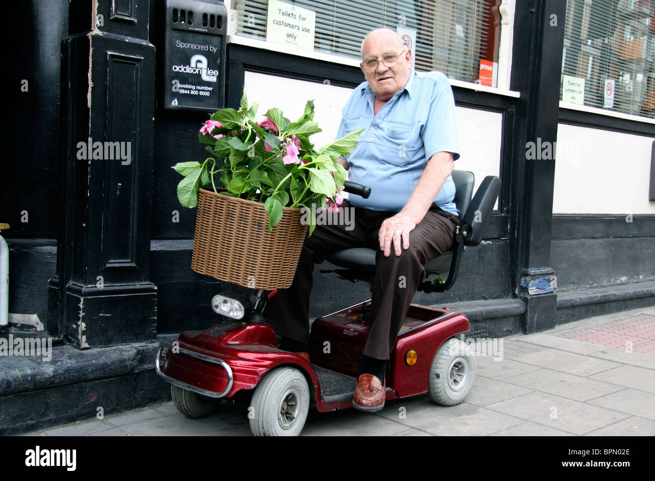 Elderly Man On His Mobility Scooter Outside A Pub In East