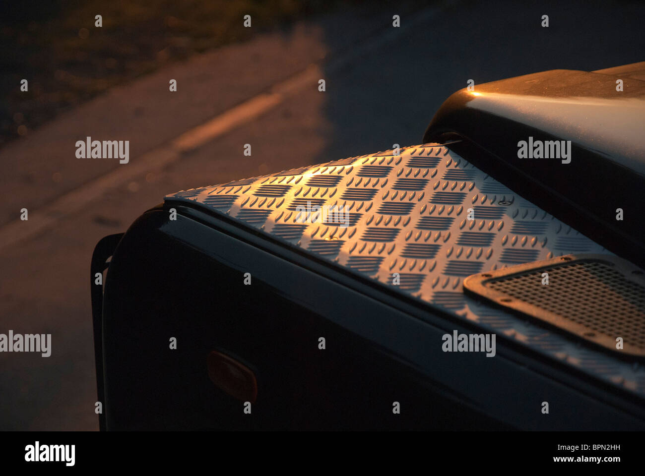 Chequered metal plate on top of Land Rover Defender wheel arch - Stock Image