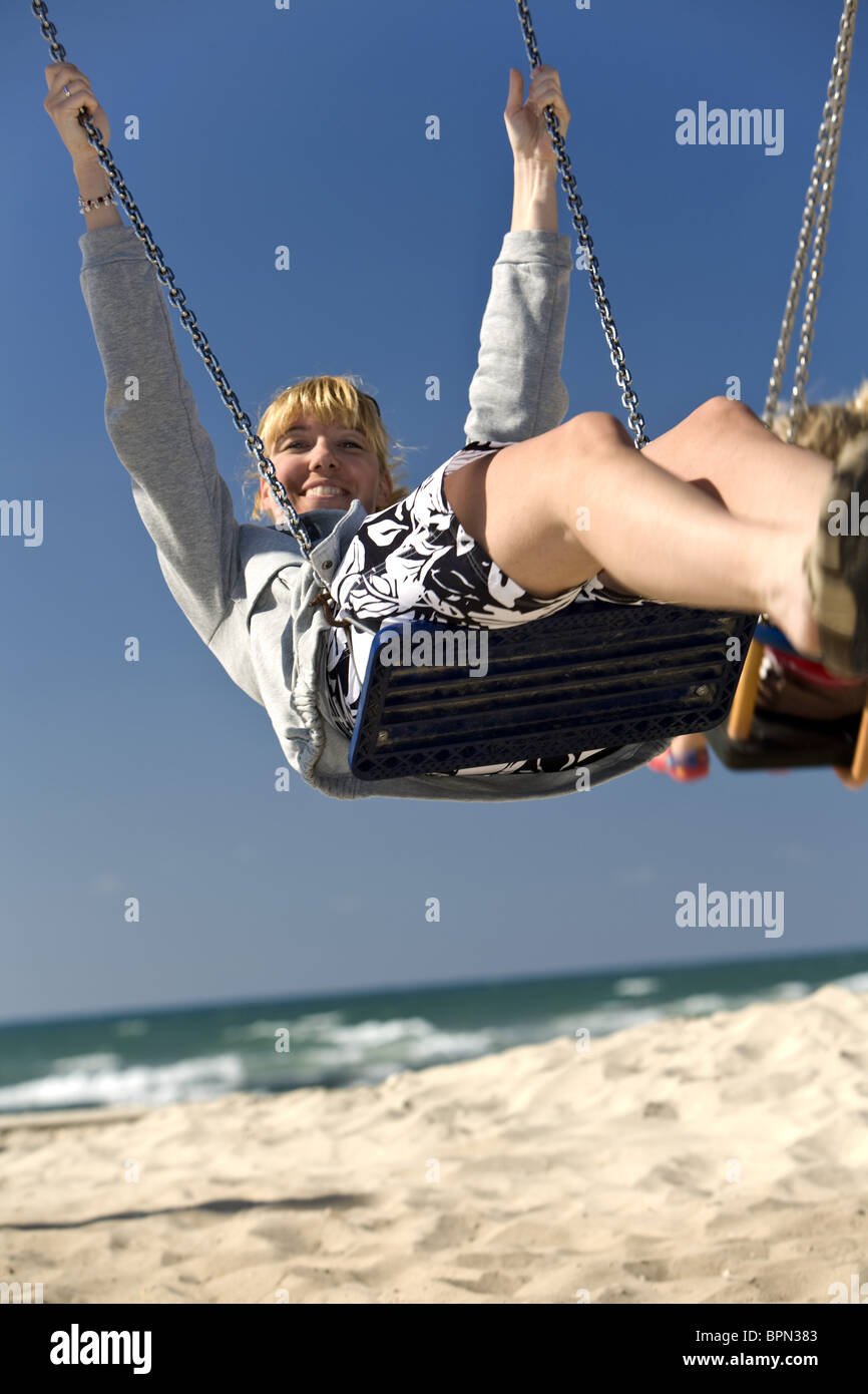 Woman on a swing on Mezizim Beach in Tel Aviv, Israel, Middle East - Stock Image