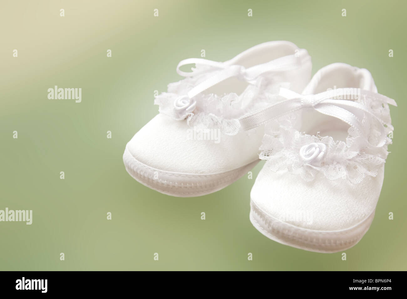 f5af46199997 White baby shoes for christening on green background Stock Photo ...