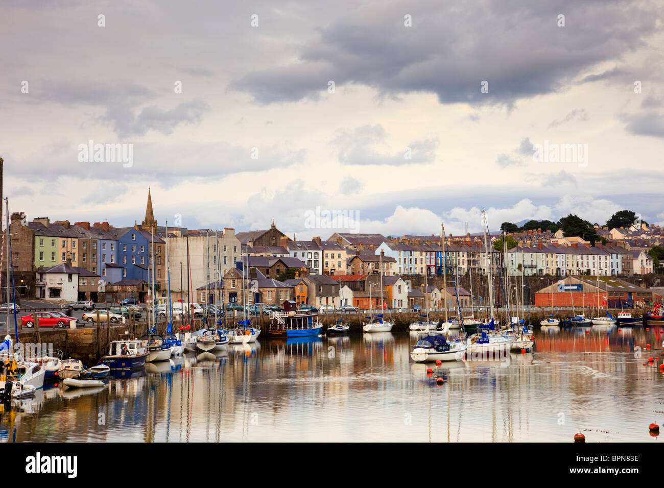Boats moored by fishing port quay on Afon Seiont River with riverside town houses on waterfront beyond. Caernarfon, - Stock Image