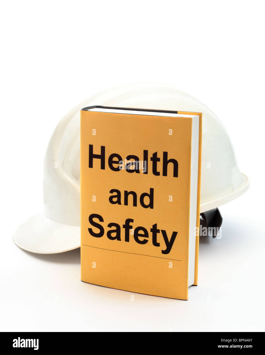 Book with words 'health and safety' on cover with safety helmet behind - Stock Image