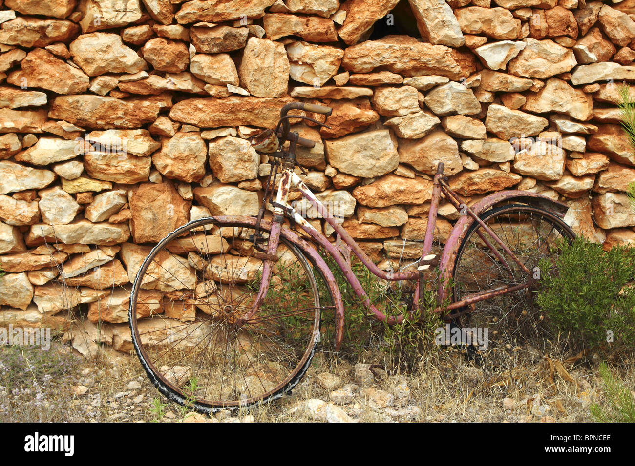 aged weathered bicycle vintage masonry stone wall in Formentera Balearic islands - Stock Image