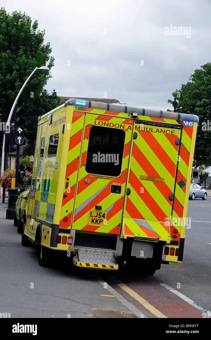 London Ambulance parked half on pavement with lights flashing whilst attending an emergency Stock Photo