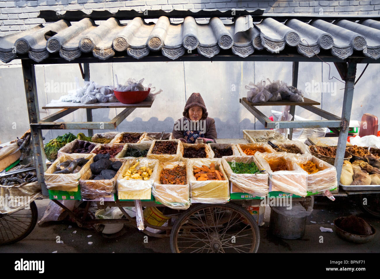 A happy lady tenders her market food stall in the old backstreets of Beijing. Stock Photo