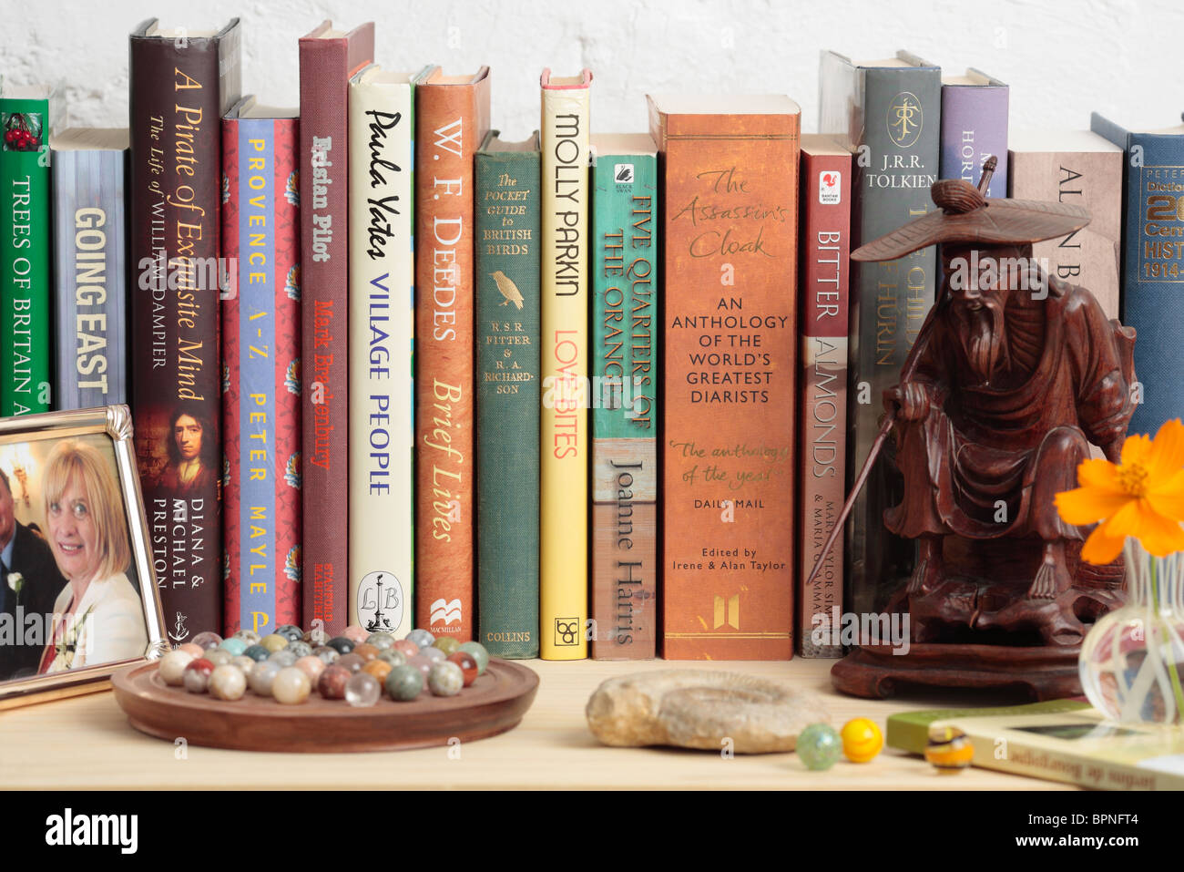 Bookshelf of Mixed Books, Carved Figure, Ammonite Fossil, Game of Solitaire and Picture Frame. - Stock Image
