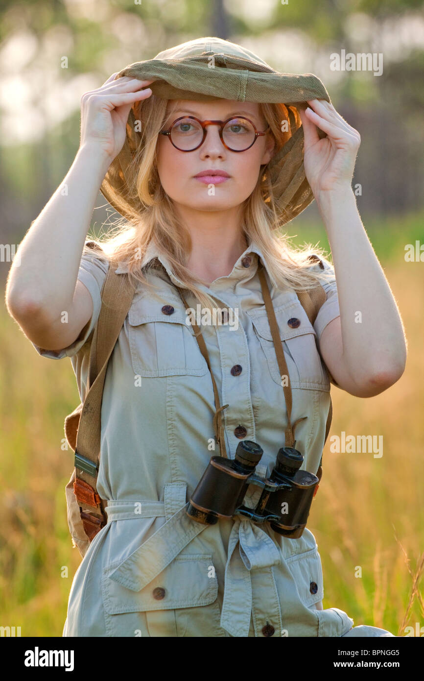 Portrait of young woman standing in field with mosquito net hood and binoculars - Stock Image