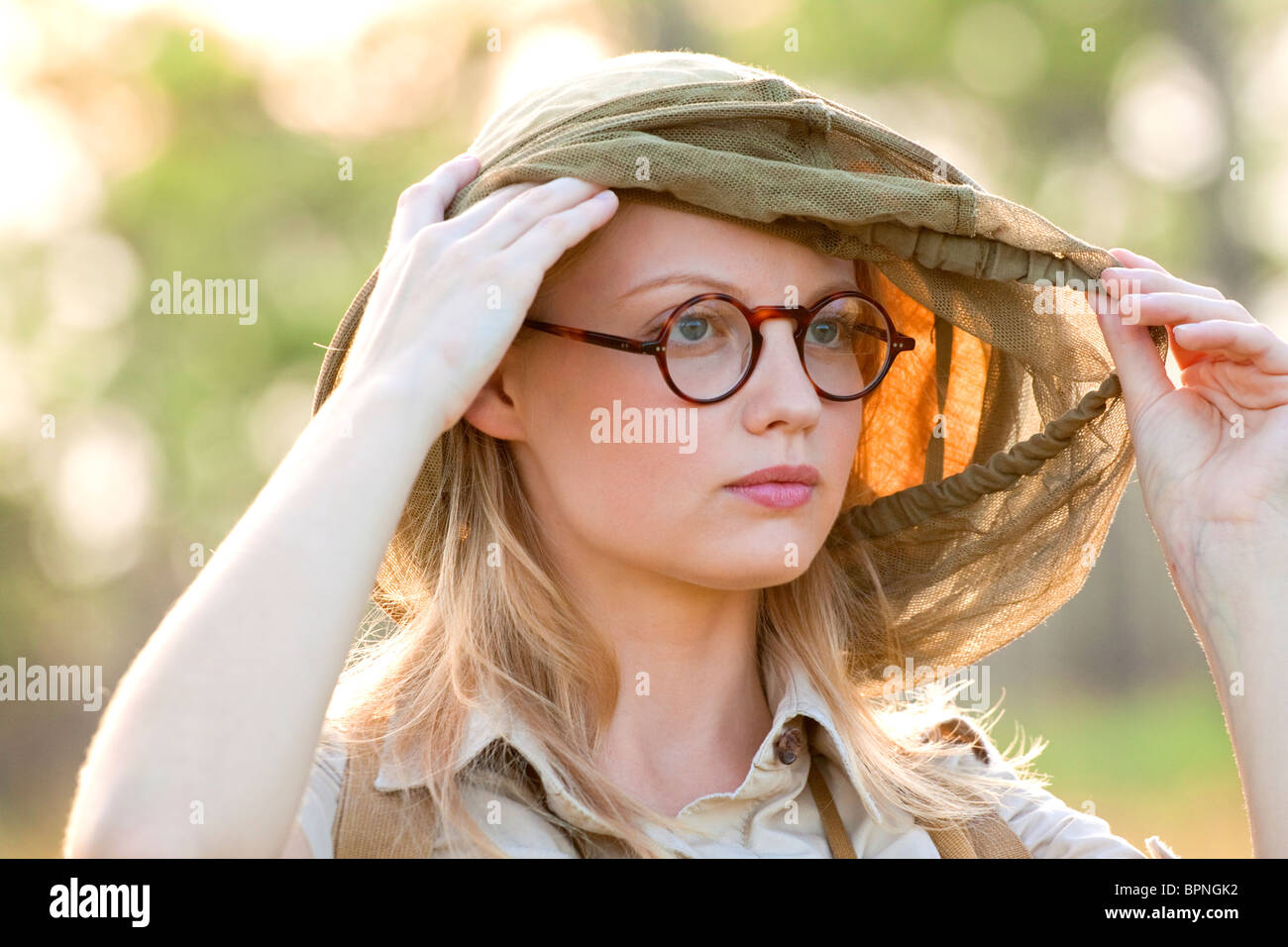 Young woman in eye glasses wearing a mosquito net hood - Stock Image