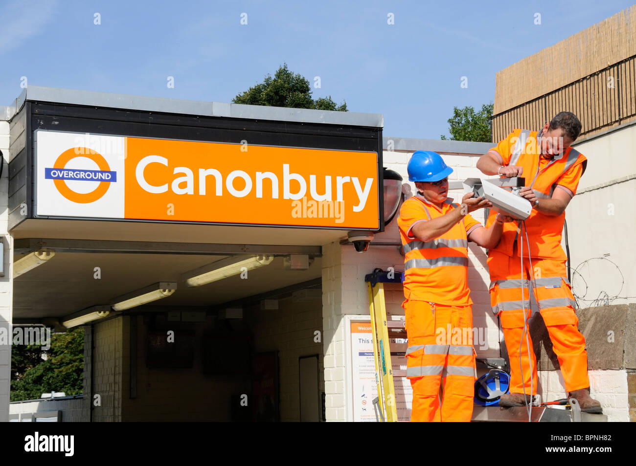 RAIL WORKERS FITTING SECURITY CAMERA AT CANONBURY TRAIN OVERGROUND STATION IN LONDON UK - Stock Image