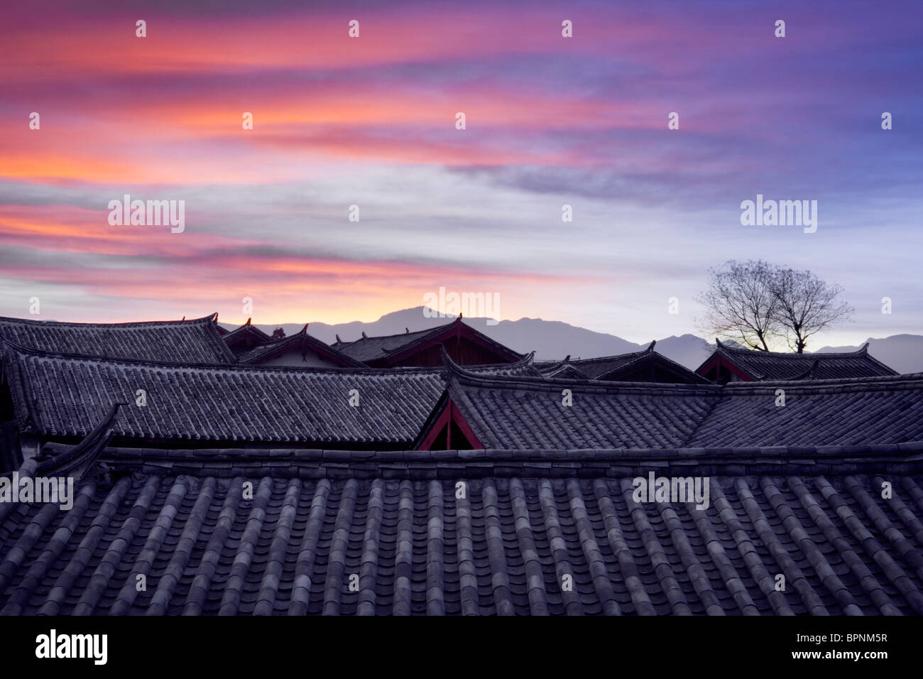 The sun rises on tiled roofs,historic town of Lijiang,UNESCO World Heritage Site,Yunnan Province,People's Republic - Stock Image