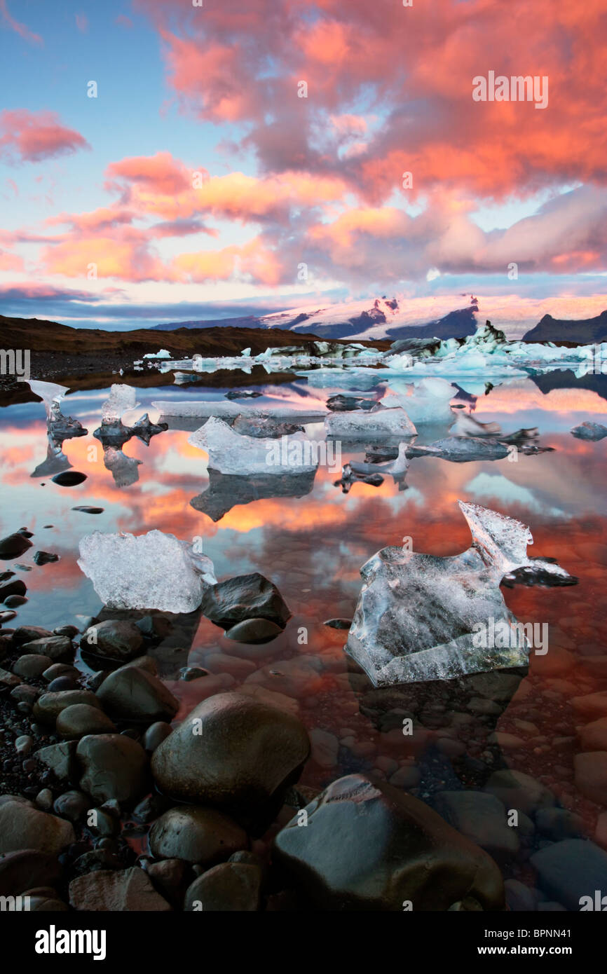 Sunrise light warms the clouds over the strange ice forms in Jokulsarlon Lagoon in Iceland - Stock Image