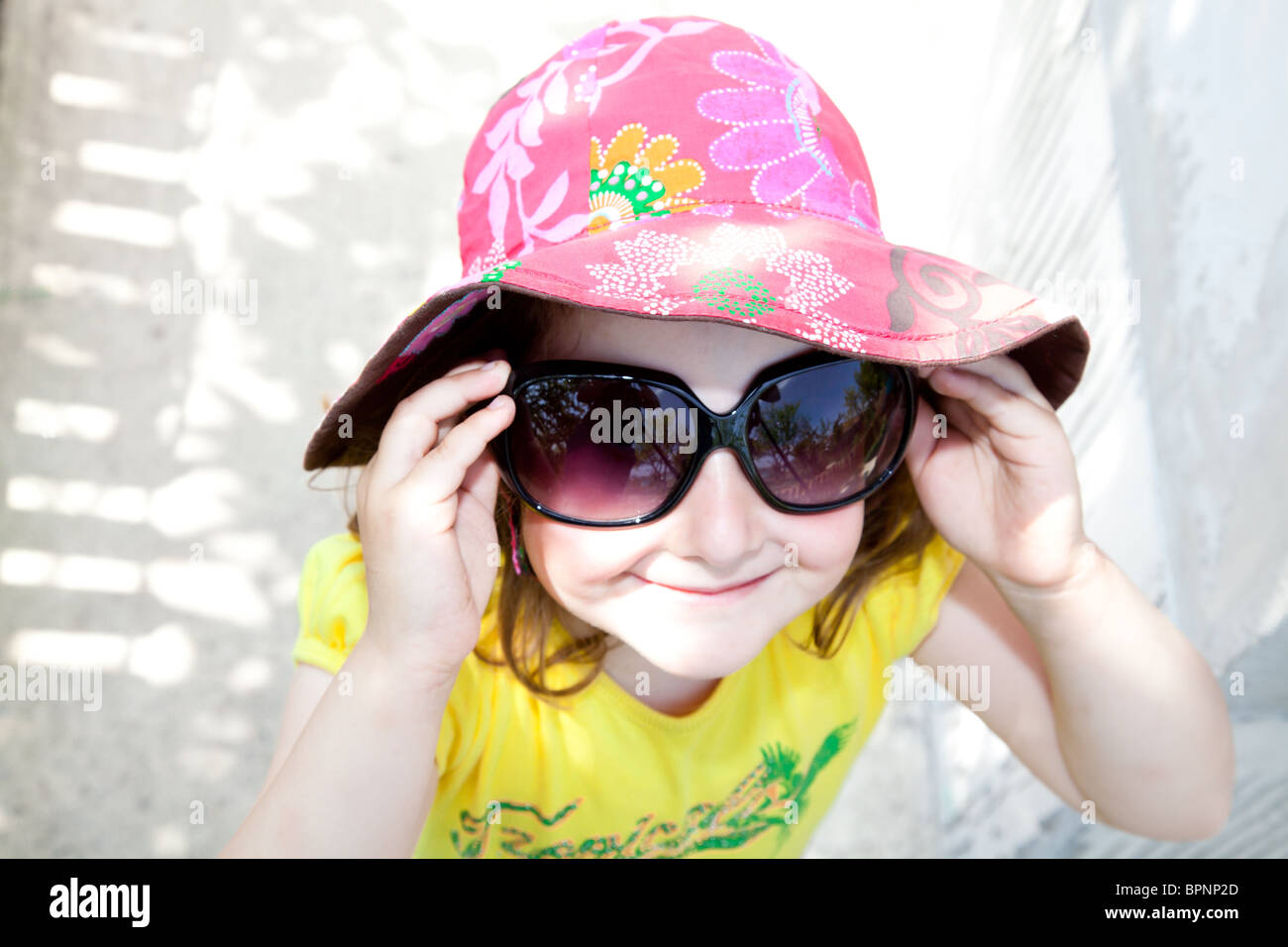 9540cd31cae8 Little girl wearing a pink hat trying on her mom's sun glasses. - Stock  Image