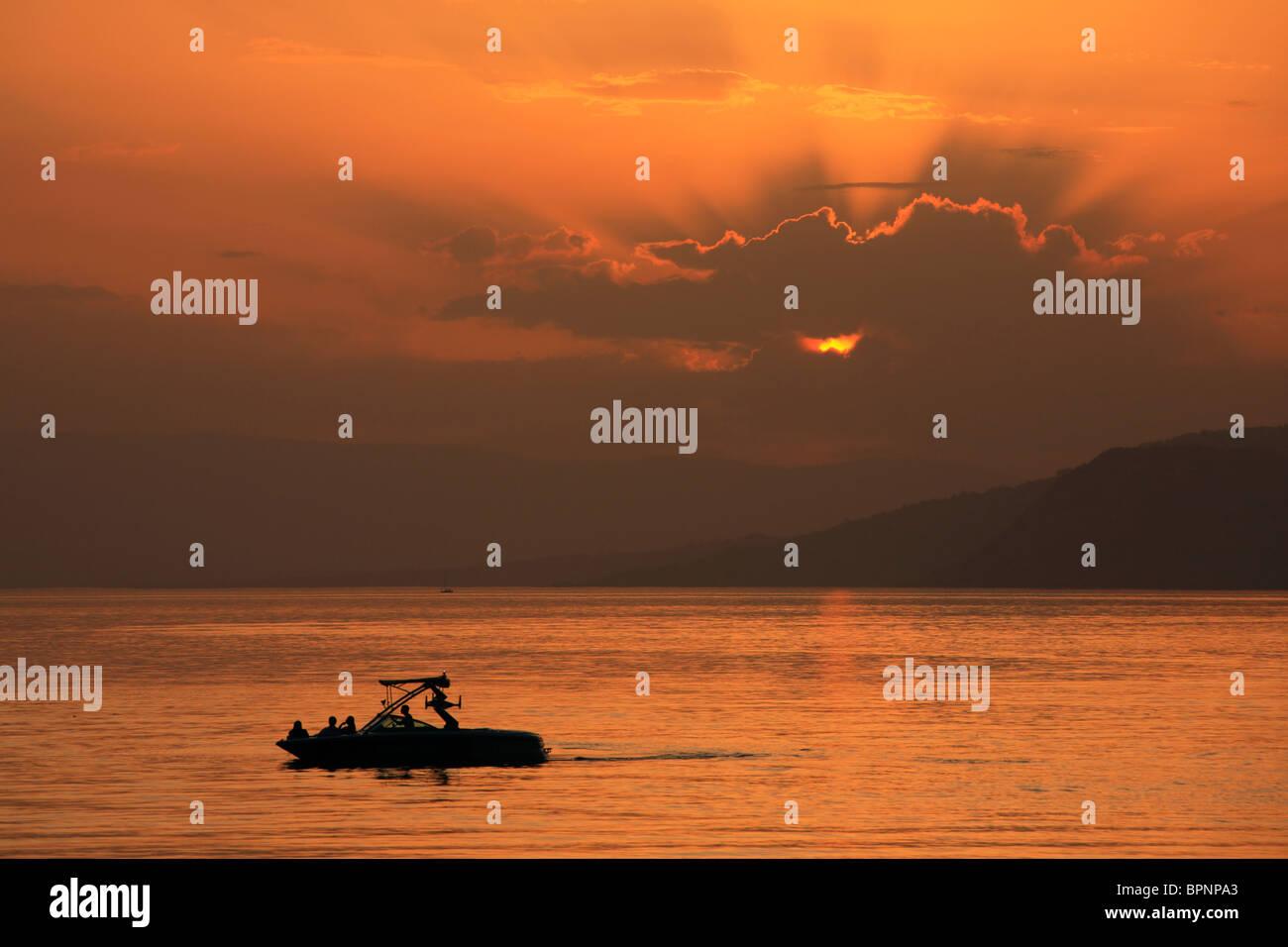 Crepuscular rays make for a dramatic sunset over Lake Geneva in Switzerland - Stock Image