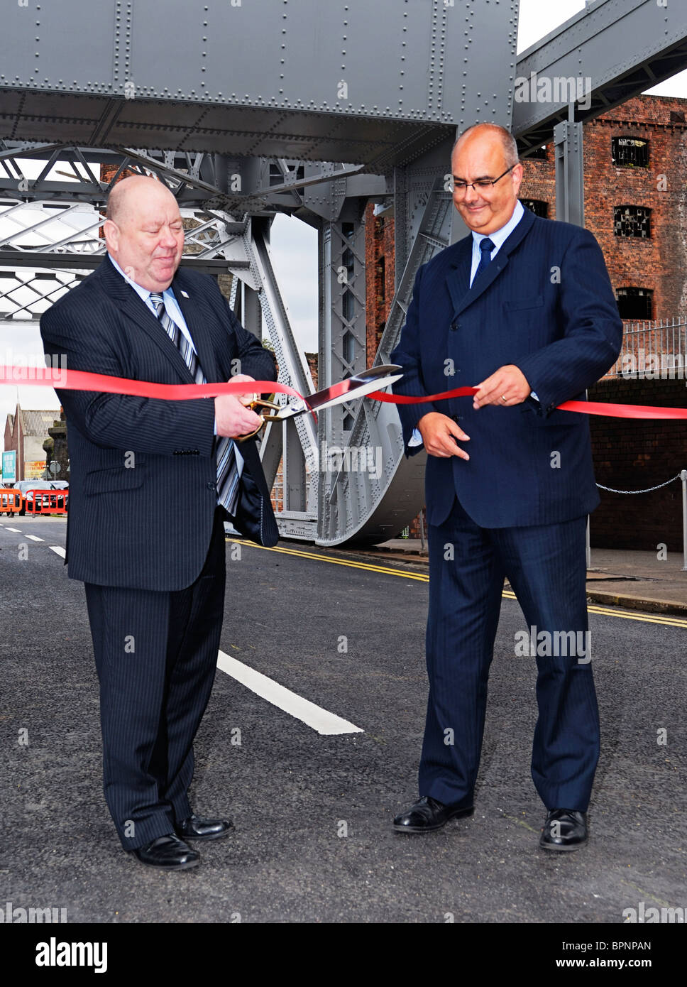 Local councillor Joe Anderson and Ian Porritt cutting the ribbon at the opening ceremony for the Stanley Dock bascule - Stock Image
