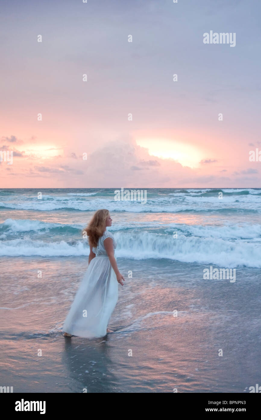 Woman in gown standing by the sea - Stock Image